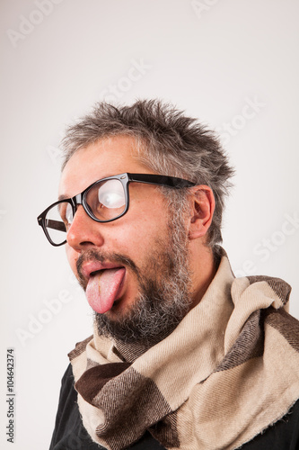Photo  Crazy looking old man with grey beard with nerd big glasses show tongue rolling