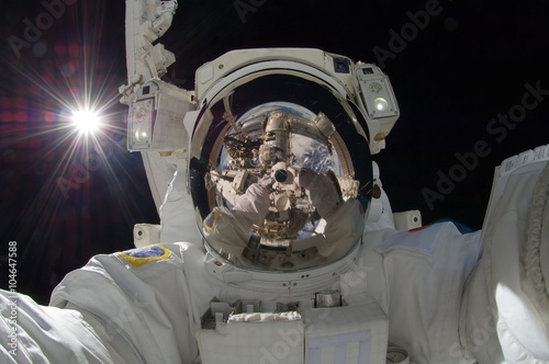 Fotografie, Obraz  close up view of floating astronaut with a reflection of the space station showi
