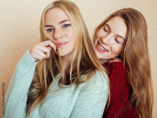 Photo  Two young girlfriends in winter sweaters indoors having fun