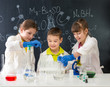 three little students on chemistry lesson in lab