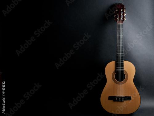 Akustische Gitarre auf einem schwarzen Hintergrund (mit Kopienraum) Fototapete