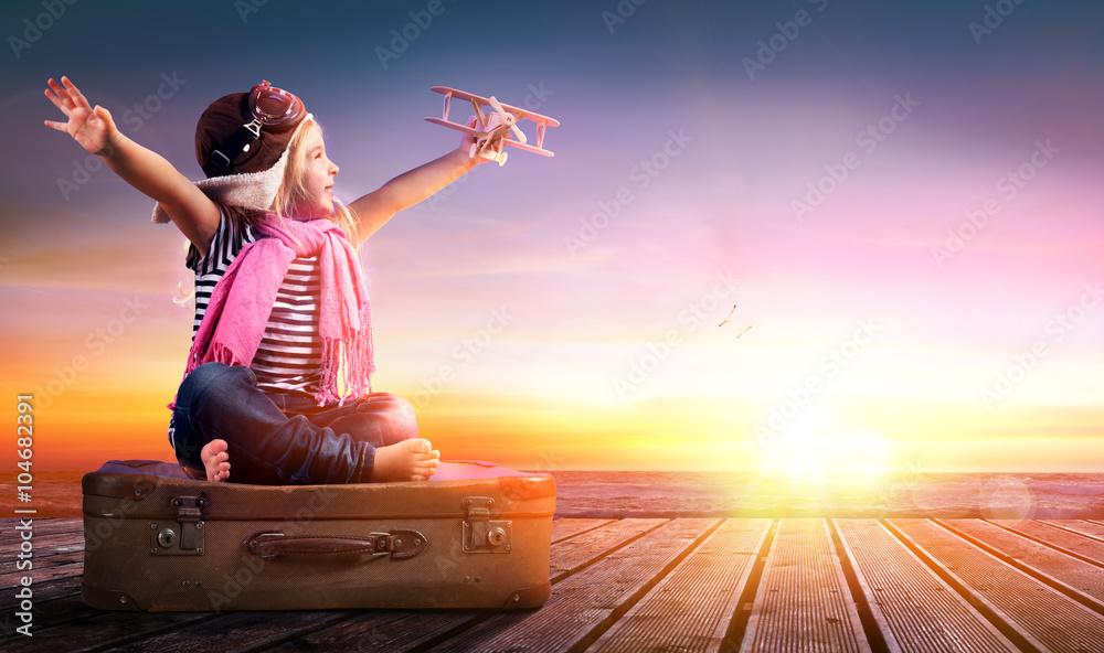 Fototapeta Dream journey - Little Girl On Vintage Suitcase At Sunset