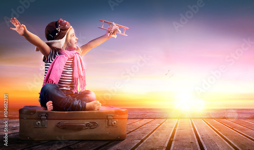 obraz lub plakat Dream journey - Little Girl On Vintage Suitcase At Sunset