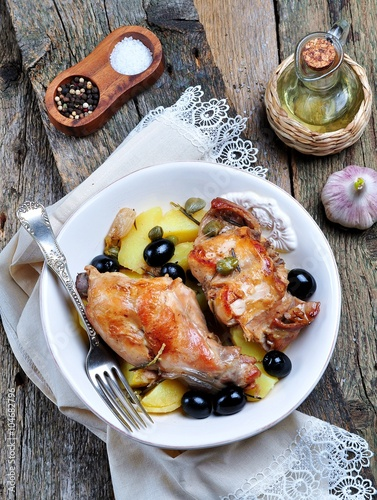 obraz dibond Roast rabbit in white wine with rosemary, olives and capers