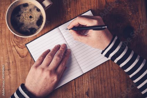 Valokuvatapetti Woman drinking coffee and writing a diary note
