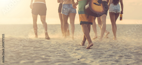 Group of friends walking on the beach at sunset. - 104717555