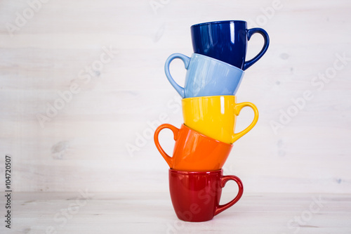 a stack of colorful coffee cups on a white wooden background