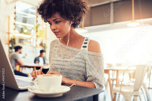Attractive young woman with earphones using laptop at cafe