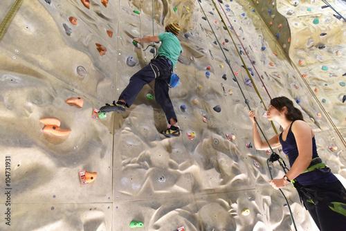 Fotografie, Obraz  Klettersport in einer Kletterhalle - Frau sichert Mann beim klettern an Felswand