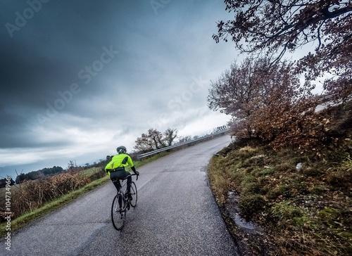 Ciclista percorre una strada in salita sotto la pioggia Poster