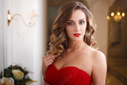 Plagát  Beautiful young woman with perfect make up and hair style in gorgeous red evenin