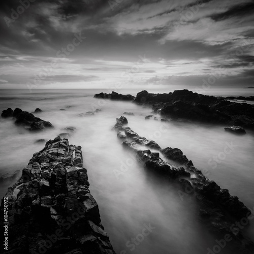 Long exposure and black and white image of Rocky Beach Poster