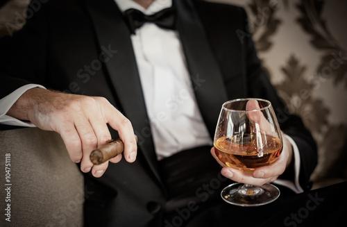 Fotografie, Obraz  Gentleman držící sklenku koňaku a doutník