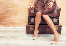 Woman Sitting On Old Suitcases