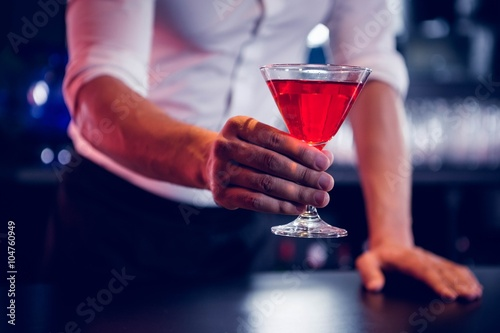 Photo  Bartender serving a red martini