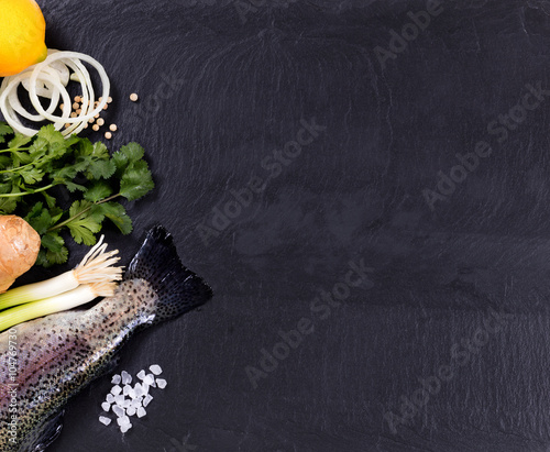 Photo  Fresh whole fish and herbs displayed on natural slate