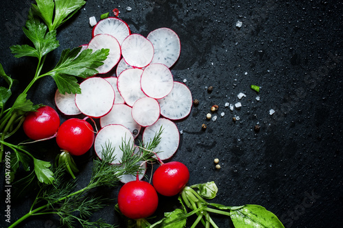 Sliced radish, parsley, dill, salt and spices on a dark backgrou