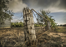 Weathered Old Fence Post And Rusted Wire On A Rural Property In Outback Australia