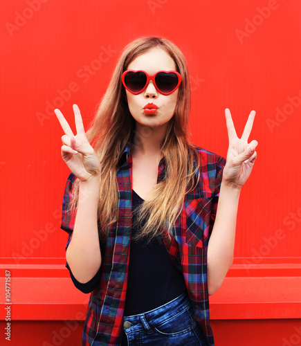 Pretty woman in red sunglasses blowing lips kiss over colorful b Wall mural