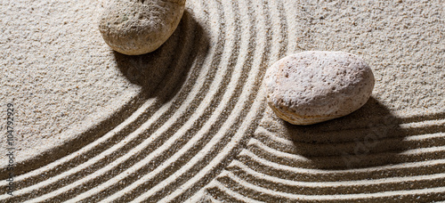 Photo sur Plexiglas Zen pierres a sable zen sand still-life - two stones across lines to give different directions for concept of difference or evolution with peace, top view