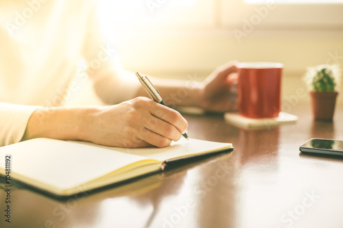 Fotografía  Female hands writing on notebook