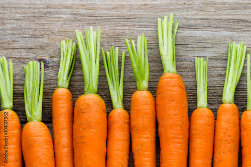 Fresh carrots bunch on rustic wooden background.
