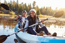 African American Couple Rowing Kayak On Lake