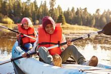 Two Children Rowing Kayak On Lake
