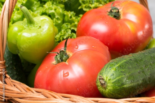 Fresh vegetables covered with water drops in basket. Organic Tomatoes, cucumber, pepper and vibrant green lettuce from the market. Fresh raw food. - 104826785