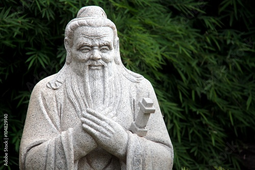 Valokuvatapetti Chinese statue of Confucius with bamboo leaves background