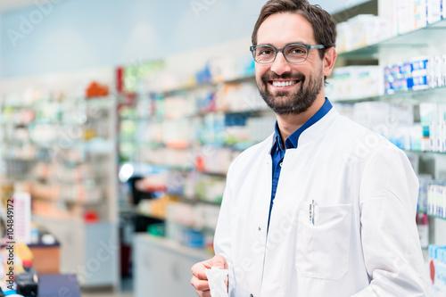 Deurstickers Apotheek Apotheker in Apotheke steht vor Regal mit Medikamenten