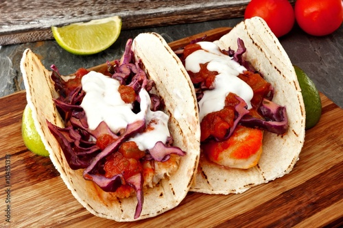 Fényképezés  Two spicy fish tacos with red cabbage lime slaw, salsa and sour cream on wooden
