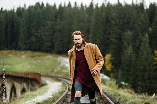Fotografía  brutal bearded man walks on the tracks