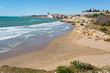 Beach and rocky coast with view of the beautiful town of Sitges,