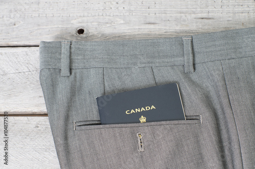 Fényképezés  Canadian passport in grey pant  back pocket against wooden backg