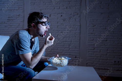 television addict man on sofa watching TV and eating popcorn in funny nerd geek Canvas Print