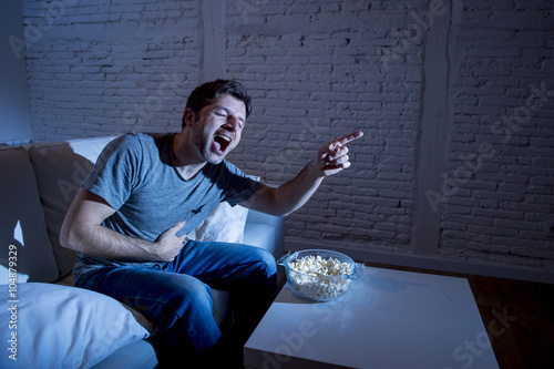 Photo  young television addict man sitting on home sofa watching TV and eating popcorn