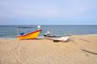 orange and white color fiber boat on the sandy beach