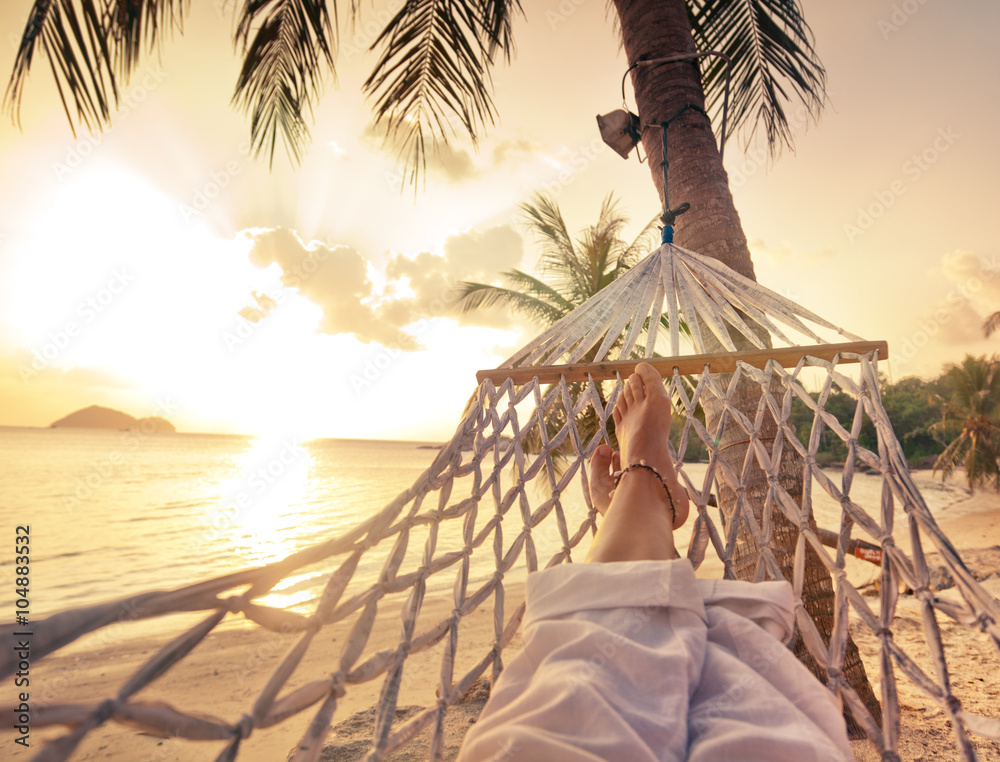 Fototapeta Female legs in a hammock on a background of the sea, palm trees and sunset. Vacation concept