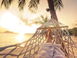 Female legs in a hammock on a background of the sea, palm trees and sunset. Vacation concept