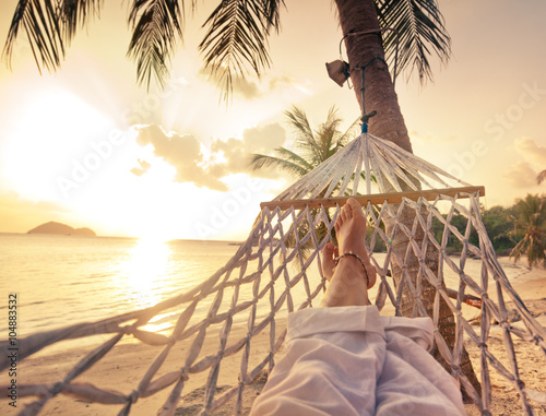 Female legs in a hammock on a background of the sea, palm trees and sunset Wallpaper Mural