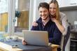 junges paar sitzt am küchentisch und schaut lachend auf den laptop