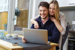 lachende frau zeigt ihrem mann etwas am laptop