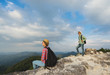Young backpackers enjoying a valley view from top of a mountain. Travel concept. Focus on the woman