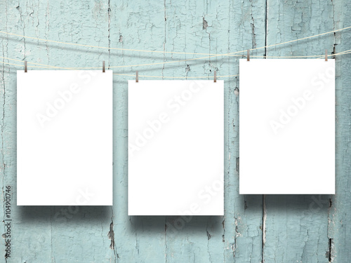 Fotografia  Close-up of three hanged paper sheets with pegs on weathered aqua wooden boards