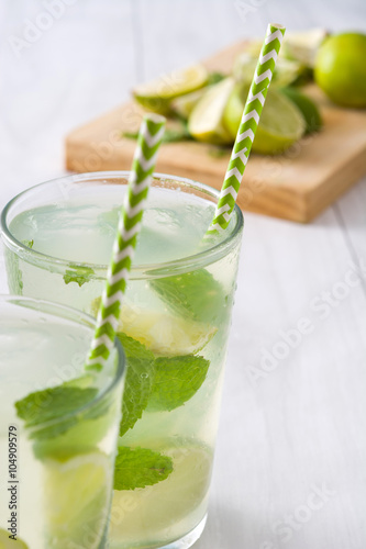 Fotografia  Summer drink. Fresh mojito with lime and mint. Blue background