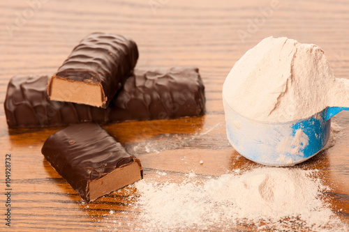 Fotografia  Whey protein powder in measuring scoop and chocolate protein bar