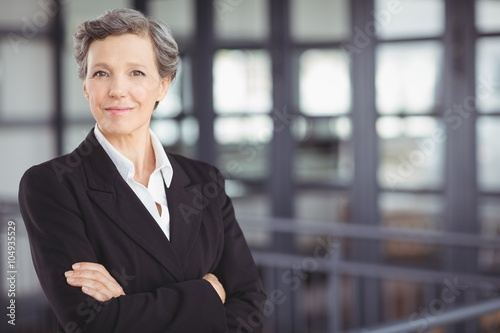 Confident businesswoman standing by railing