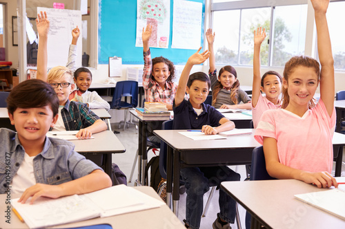 Fotografía  Elementary school kids in a classroom raising their hands