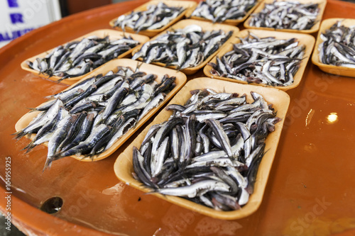 Group of sardines on a colorful bench for sale in fresh